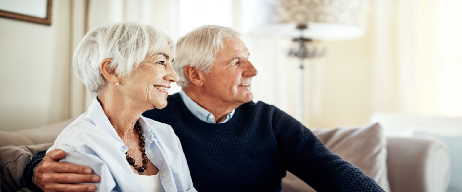 senior couple smiling while sitting together on a couch