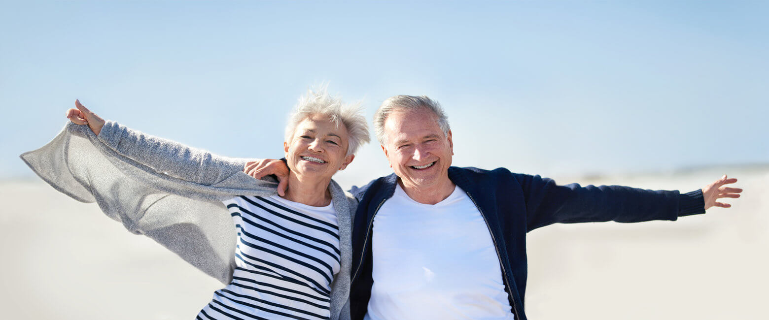 Portrait of a happy senior couple having fun with their arms outstretched at the beach