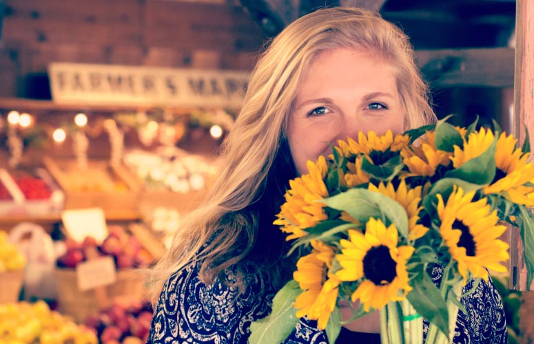 Blonde young woman hides her yellow teeth with a bouquet of yellow sunflowers at a farmers market