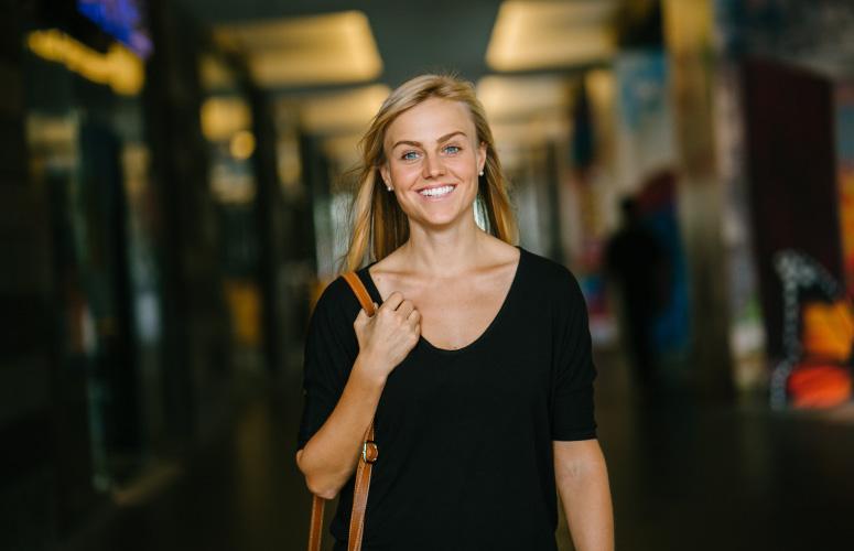 Blonde woman wearing a black shirt and brown shoulder bag smiles with custom-made dental veneers