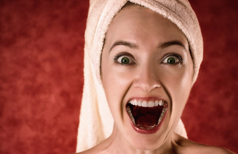 woman with a towel on her head and open mouth after using mouthwash