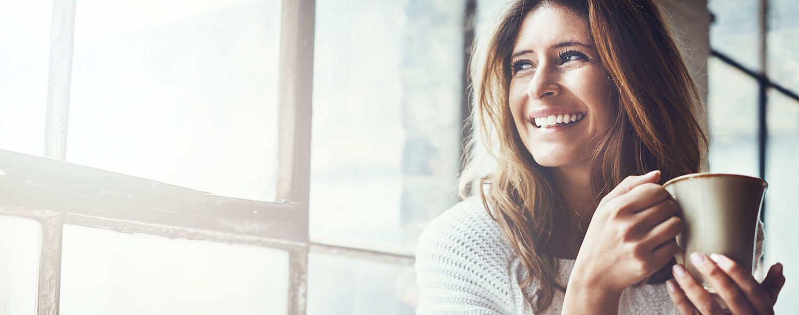 Woman looking out window smiling holding cup of coffee