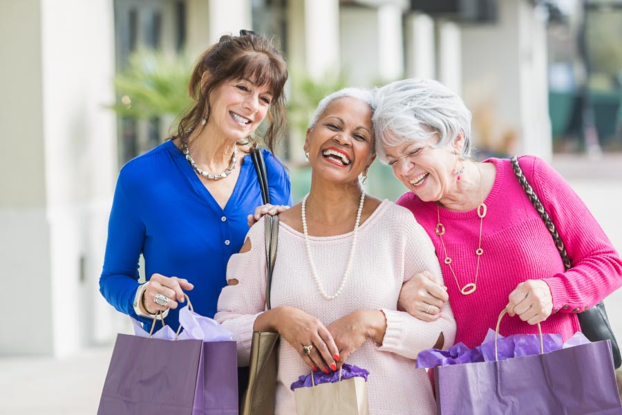 3 Older laughing women of mixed ethnicity walking arm in arm down the sidewalk with shopping bags