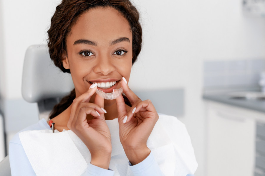 Pretty, dark skinned girl in the dental chair is smiling and holding her clear aligner in front of her face.