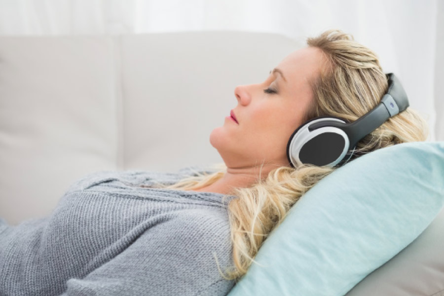 Woman with headphones in the dental chair to handle dental anxiety.