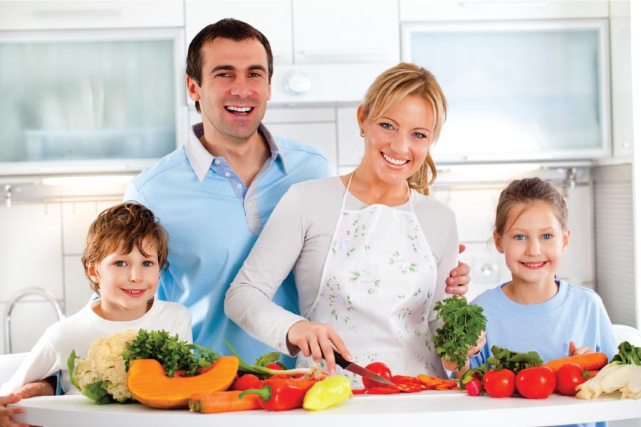 Family of four in the kitchen with a counter full of healthy fruits and vegetables.